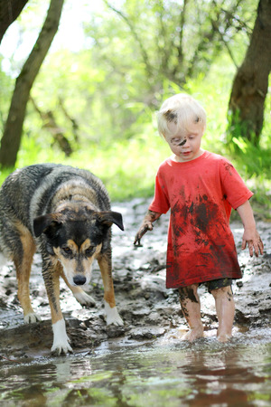 A young boy child and his German Shepherd mix dog are covered in mud and playing outside on the beach of a river in the woods
