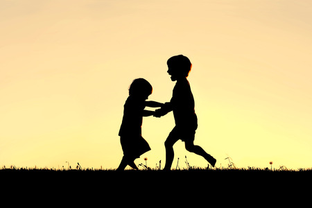 A silhouette of two happy little children, a young boy and his baby brother, holding hands and dancing and playing in front of a sunset in the sky  Stock Photo