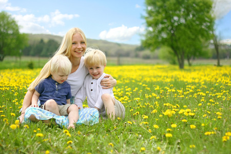A happy young mother is siitting in a Dandelion flower meadow with her two little children on her lap, on a beautiful spring day  photo