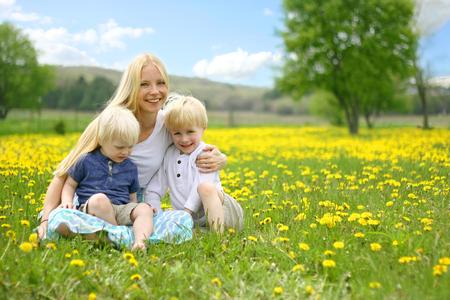 familia cristiana: Una madre joven y feliz se siitting en un prado de la flor diente de león con sus dos pequeños hijos en su regazo, en un hermoso día de primavera Foto de archivo
