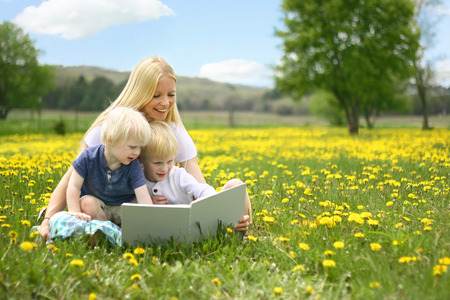 A happy young mother is sitting outside in a meadow of yallow Dandelion flowers, reading a story book to her cute children on a lovely Spring day