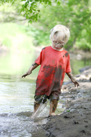 A cute, dirty little boy child is playing outside, splashing in a river on a muddy beach on a summer day