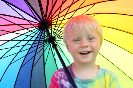 litle: a happy little two year old boy child is smiling as he stands outside under a rainbow colored umbrella to keep dry from the rain. Stock Photo