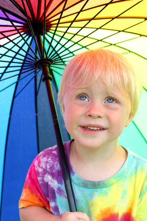 two year old: a happy little two year old boy child is smiling as he stands outside under a rainbow colored umbrella to keep dry from the rain. Stock Photo