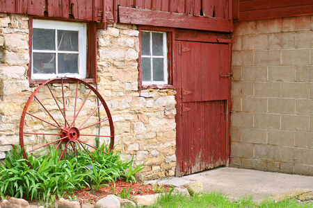 barndoor: An antique metal wagon wheel is leaning up against an old stone barn wall and rusic red barn door  Stock Photo