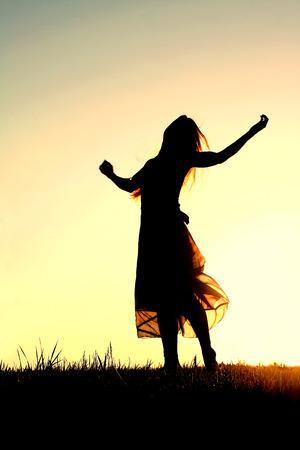 長いブロンドの髪の長いスカートをはいている女性はダンスと賛美の中には夕方の空に対してシルエット