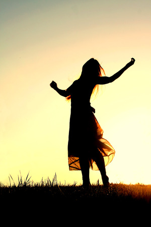 A woman wearing a long skirt, with long blonde hair, is dancing and praising God, while silhouetted against the evening sky Archivio Fotografico