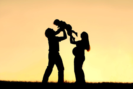 A silhouette of a happy family of three people, father, child and pregnant mother, are celebrating and praising God outside at sunset  Stock Photo