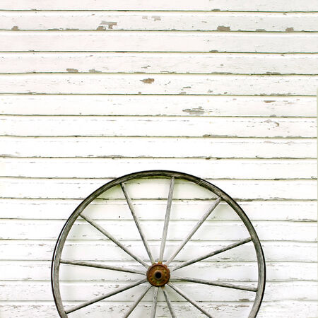 wheel house: An old, antique wooden wagon wheel is leaning up against a white rustic wall background, with peeling paint  Stock Photo