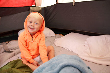 two year old: A happy young boy child is waking up in a tent after spending the night camping.