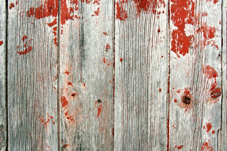 A background of rustic, aged barnwood boards, with peeling red paint. 写真素材
