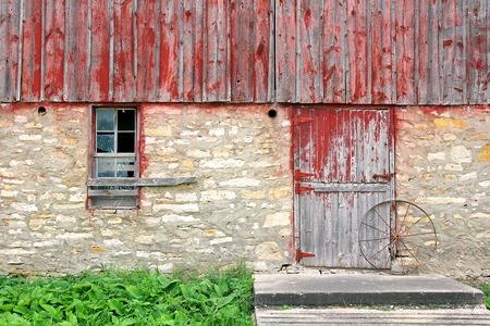 barnwood: La pared exterior que incluye una ventana y barnwood puerta rota con rueda de carro de un viejo granero banco hist�rico abandonado.