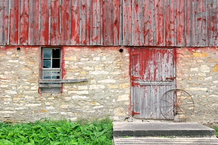 The exterior wall including a broken window and barnwood door with wagon wheel of an old abandoned historic bank barn. photo