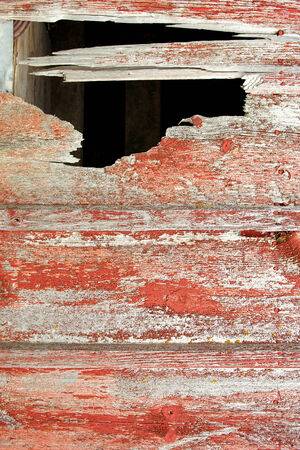old red barn: Rustic aged barnwood background with large hole in wall of barn.