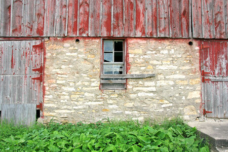 barnwood: A broken window is seen between two wooden doors with peeling red painted barnwood, on an old abandoned barn.