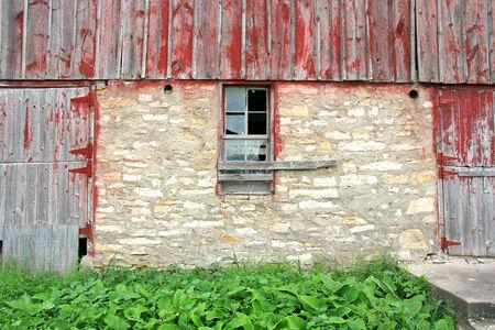 barnwood: Una ventana rota es visto entre dos puertas de madera con peeling barnwood pintado de color rojo, en un viejo granero abandonado.