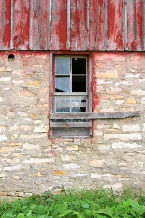 barnwood: A broken window framed in weathered wood is centered on an old barn building.