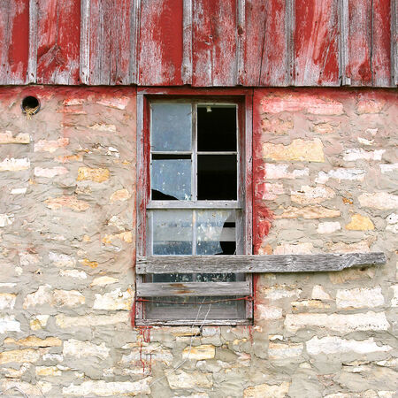 A broken window framed in weathered wood is centered on an old barn building.