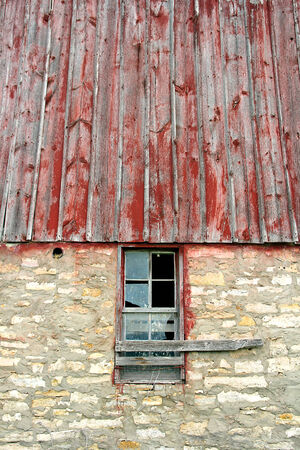 The glass is broken on an old window framed with weathered barnwood on a vintage barn. Stock Photo