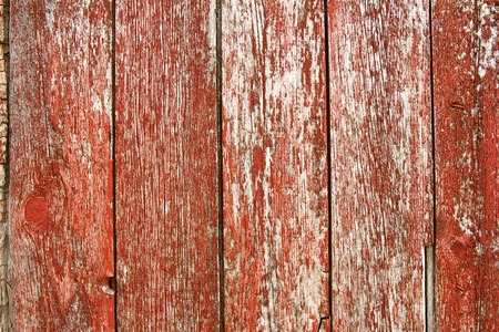 A background of old red barnwood with peeling paint on the exterior of a barn