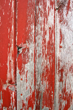 red wall: A background of rustic, aged barnwood boards, with peeling red paint  Stock Photo