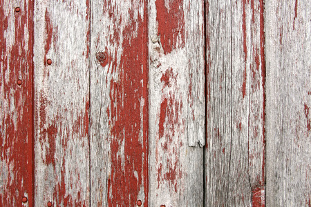 A background of rustic, aged barnwood boards, with peeling red paint  Stock Photo