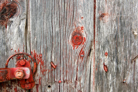 A background of rustic, aged barnwood boards, with peeling red paint, and a metal old latch  photo