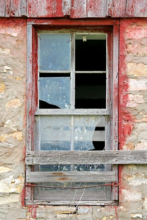 The glass is broken on an old window framed with weathered barnwood on a vintage barn  photo