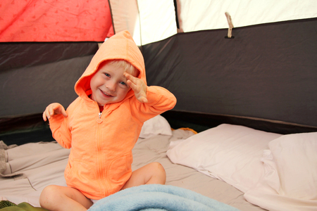 A happy young boy child is waking up in a tent after spending the night camping