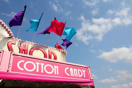 cotton candy: The roof of a carnival cotton candy sale stand has colorful flags on it in front of a blue sky