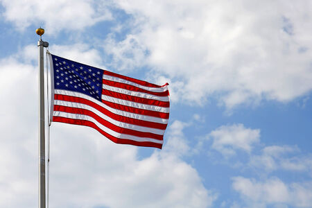 A red, white and blue American Flag is blowing in the wind in front of a cloudy blue sky  Banco de Imagens