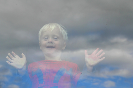 Vista desde fuera de la ventana, como un niño pequeño feliz que tiene las manos y la cara presionado el vaso y se mira hacia fuera Foto de archivo - 30596578