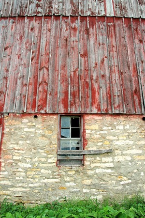 An exterior wall with a broken window on an old abandoned historic Bank Barn  Stock Photo