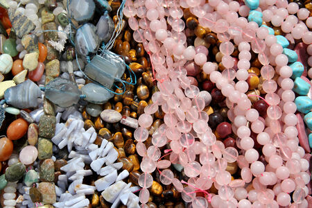 A close up background of a collection of colorful glass and stone womens fashion bead jewelry for sale in a basket. photo