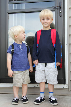 A young child is looking up to his big brother with admiration as they wear backpacks on the first day back to school for kindergarten. Reklamní fotografie