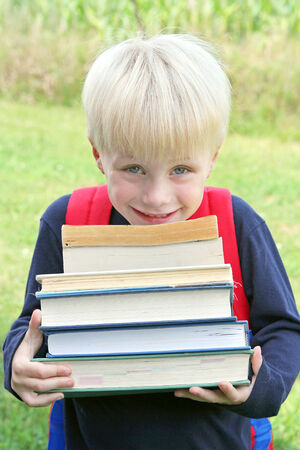 A happy young child is carrying a big stack of heavy school books.