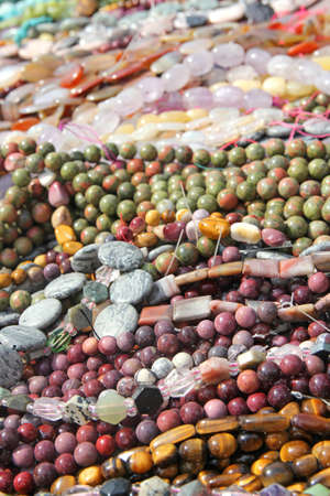 A close up of a collection of colorful glass and stone womens fashion bead jewelry for sale in a basket. photo