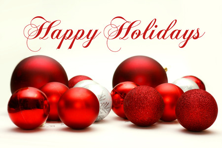 happy holidays text: A Collection White and Red Sparkling Christmas Bulb Ornaments are Scattered on a White Background, with the text Happy Holidays. Stock Photo