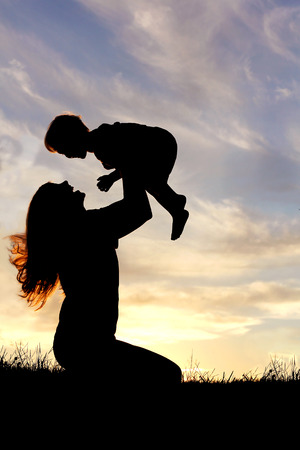 bliss: A silhouette of a happy young mother, laughing as she plays with her toddler child and lifts him over her head outside at sunset.