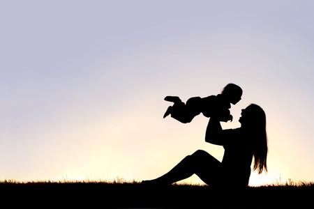 Una silueta de una mujer, madre de risa sentado en la hierba en la puesta del sol, el levantamiento de su bebé en el aire. Foto de archivo