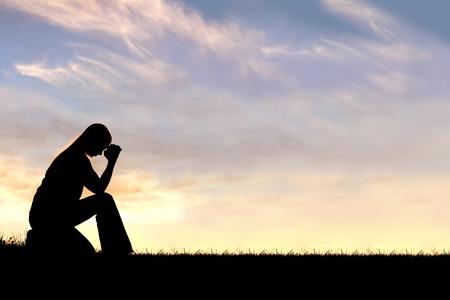 젊은 기독교 여자의 실루엣 일몰 동안 외부 그녀의기도에 머리와 절망을 굴복한다. 스톡 콘텐츠