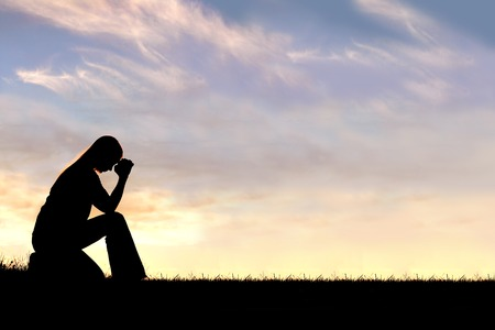 ansiedad: Una silueta de una joven cristiana se inclina la cabeza en la oración, y la desesperación al aire libre durante la puesta del sol. Foto de archivo