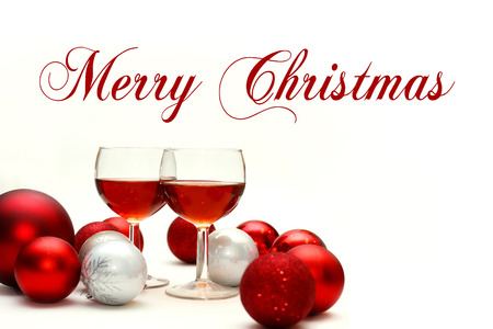 recieve: Two wine glasses filled with red wine sit on an isolated white background with words Merry Christmas, surrounded by silver and red sparkling Christmas Bulb Decorations