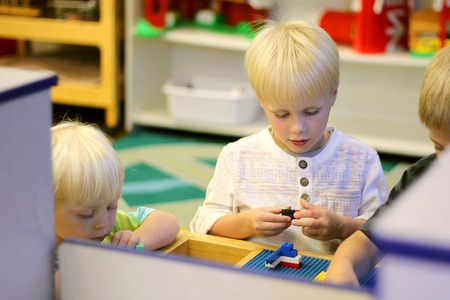 Some young preschool children are at their school classroom playing with building block toys.