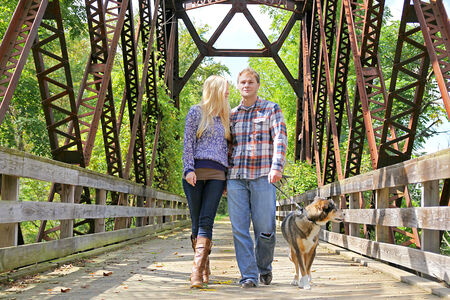 An attractive young married couple in their thirties are walking their German Shepherd mix breed dog across a bridge on a forest path in Autumn. photo