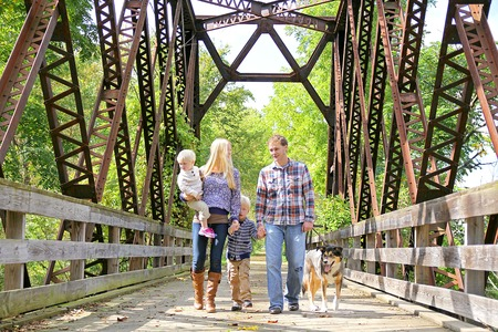A happy family of four people, including mother, father, young child, and toddler brother are walking outside across a metal bridge in the Autumn Forest with their German Shepherd rescue dog.