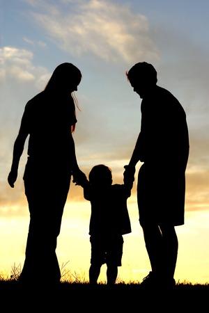 niños caminando: Una familia feliz de tres personas, madre, padre y niño, son la celebración hads y caminando hacia la puesta de sol, recortada contra el cielo.