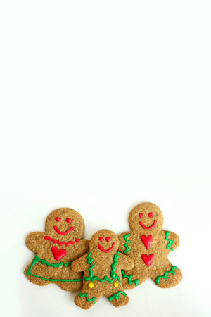 A  Christmas Gingerbread cookie family of man, woman, and child is isolated on a white background, with copy-space for text or to use as a greeting card. photo