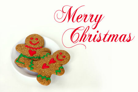 A Christmas gingerbread man cookie with hearts on his shirt is laying on a white plate with a gingerbread woman, on a white isolated background, cursive text written Merry Christmas. photo