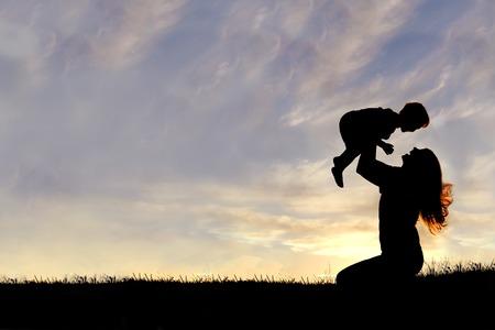 mujer hijos: Una silueta de una joven madre feliz, riendo como ella juega con su hijo pequeño y lo levanta sobre su cabeza fuera, aislado contra la puesta de sol.